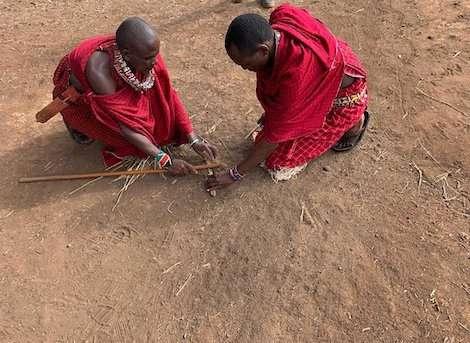 Masai warriors lighting fire using sticks kenya